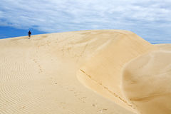 Walking through Time. A hiker walks up the steep sandy slopes of the White Sand Dunes in Vietnam Royalty Free Stock Photo