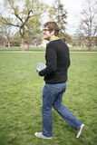 Walking to class. Male college student holding books walking on grass on campus grounds going to class Stock Image