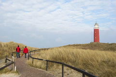 Walking to lighthouse. Two men are walking to red lighthouse Royalty Free Stock Photography