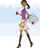 Walking to work. African American walking to work with her coffee, laptop and an apple for a snack Royalty Free Stock Photography