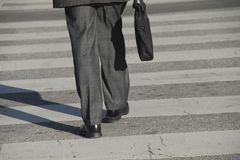 Walking to work. Businessman walking to his office carrying a briefcase Royalty Free Stock Photo