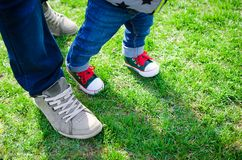 Walking toddler concept. Little baby child boy making first step holding father`s hand. First steps. Foot of father and son in stylish sneakers on the Stock Photo