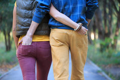 Walking together. Man and woman are walking down the alley in the park, cuddling, holding hands in the pockets Royalty Free Stock Photo