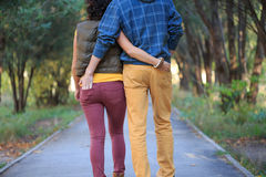 Walking together in he park. Man and woman are walking down the alley in the park, cuddling, holding hands in the pockets Royalty Free Stock Images