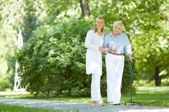 Walking together. Pretty nurse and senior patient with walking stick having a walk in park stock photos