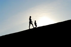 Walking together up the hill. Silhouette of two girls walking together up the hill Stock Image