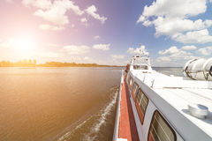 Walking tourist ship sails on the lake. The view from the deck of the ship. Sunny summer day Stock Image