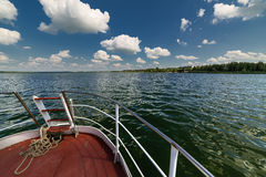 Walking tourist ship sails on the lake. The view from the deck of the ship. Sunny summer day Royalty Free Stock Image