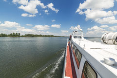 Walking tourist ship sails on the lake. The view from the deck of the ship. Sunny summer day Royalty Free Stock Photos