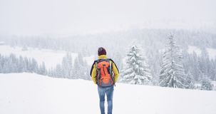 Walking tourist in the snowy forest equipped with all travel stuff , with a big orange bag , he travel in the middle of. Mountain stock footage