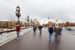 Walking tourists on a Parisian bridge Stock Images