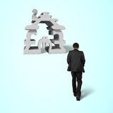 Walking toward concrete money symbol stacking building. Isolated in blue background Royalty Free Stock Photos