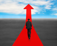 Walking toward going up red arrow Stock Photo