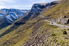 Walking Toward Mafika Lisiu. A woman looks up the road leading to the snow-capped mountains of the Mafika Lisiu Pass in Leribe, Lesotho during the dry winter stock photo