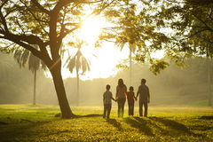 Walking towards the light. Asian family holding hands and walking towards light Royalty Free Stock Image