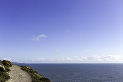 Walking track by the sea. A small walking track right by the blue sea Stock Photo