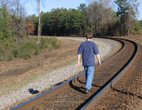 Walking on the tracks. Teen boy walking on railroad tracks in rural setting in autumn stock photos