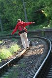 Walking on tracks. Young man walking on the railway tracks Stock Image