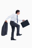 Walking tradesman with suitcase and jacket. Side view of walking tradesman with suitcase and jacket against a white background Royalty Free Stock Image
