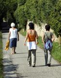 Walking trail. Two young women and an elderly lady walk along a beautiful walking trail royalty free stock photos