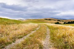Walking trail among hills and valleys covered in dry grass, south San Francisco bay area, San Jose, California stock photos