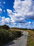 A walking trail leading to a lighthouse in the distance. stock photo