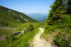 A walking trail in mountainous area on background blue sky Stock Image