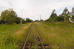 Walking on the train tracks.jpg. The train tracks and about them people walking on foot. Abandoned railroad infrastructure in Brazil. Rail transport rails stock photos