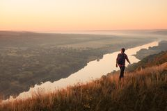Walking traveler on nature. Anonymous backpack walking on top of hill with view of river and terrain on background Stock Photography