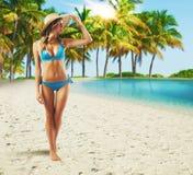 Walking on tropical beach. Bikini girl walking on a tropical beach Royalty Free Stock Image
