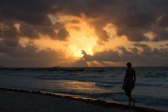Walking on Tulum coast. A boy walking on Tulum coast at & x22;playa Esperanza& x22; beach in Yucatán, Quintana Roo. Mexico. Beautiful sunrise Royalty Free Stock Image