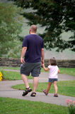 Walking with Uncle Ozzy. Thirty year old man walking with four year old girl. They are holding hands Stock Photography