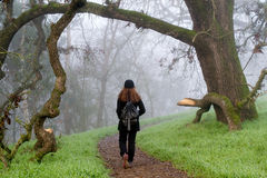 Walking into the unknown. Woman walking on a foggy trail in the winter, wearing black clothes and hat, and a backpack- uncertainty concept Royalty Free Stock Images
