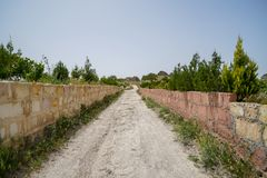 Walking unpaved rough sand road through stone brick low wall among landscape of dried and green ancient red valley with clear sky Stock Photography