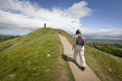 Walking up Glastonbury Tor. Glastonbury, United Kingdom - May 29, 2011: Rear view of a woman walking up the path on Glastonbury Tor towards St Michael`s Tower Stock Photos