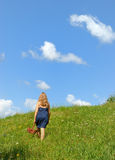 Walking up hill. Woman walking up hill in green field against blue sky Royalty Free Stock Image