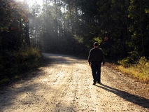 Walking up the road. Man walking up dirt road in late afternoon with rays of sun and long shadows stock images