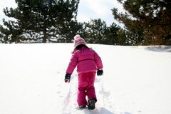 Walking up a snow covered hill. Preschooler walking up a snow covered hill stock photos