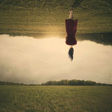 Walking upside down. Surreal woman walks through a field upside down stock photography