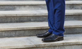 Walking upstairs: close-up view of man's leather shoes. stock photos