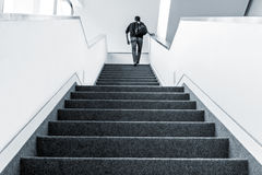 Walking upstairs indoors. Colorized picture of one man walking upstairs on staircase indoors Stock Photos