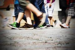 Walking on urban street. People legs walking on paved urban street Stock Image