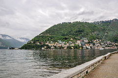 Walking view on Lake of Como and buildings in a cloudy rainy day, near Como. Royalty Free Stock Photos