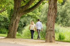 Walking in the Vondelpark. A man and woman walking through the Amsterdam Vondelpark in the Netherlands royalty free stock photo