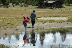 Walking by the water. Two boys walking by the river bank Royalty Free Stock Image