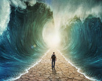 Walking through the water. A man walking through the water with the waves parted