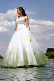 Walking on Water. A bride standing next to river in her dress Royalty Free Stock Photography