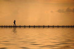 Walking on the water. A women walking on the footpath in the sea at sunset Stock Photos