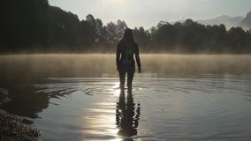 Walking in water of lake at sunrise. Morning refreshment. Silhouette of woman walking in shining water on sunrise in morning fog stock video footage