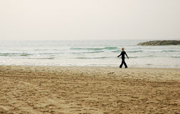 Walking on winter beach. Woman enjoying a walk on empty winter beach in bad weather stock photos